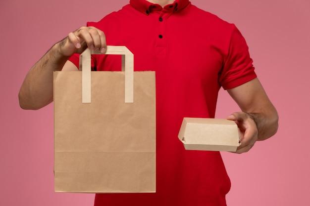 Vista frontal de perto jovem mensageiro com boné de uniforme vermelho segurando dois pacotes de comida diferentes na parede rosa