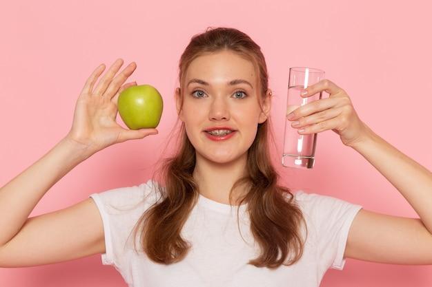 Vista frontal de perto, jovem mulher com camiseta branca segurando uma maçã verde e um copo d'água na parede rosa