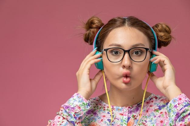 Vista frontal de perto jovem mulher em camisa com design flor e calça jeans, ouvindo música com fones de ouvido no fundo rosa