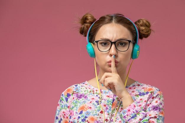 Vista frontal de perto jovem mulher em camisa com design floral e jeans azul, ouvindo música com fones de ouvido ed no fundo rosa
