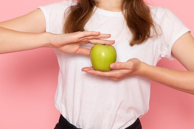 Vista frontal de perto jovem mulher em camiseta branca segurando uma maçã verde na parede rosa