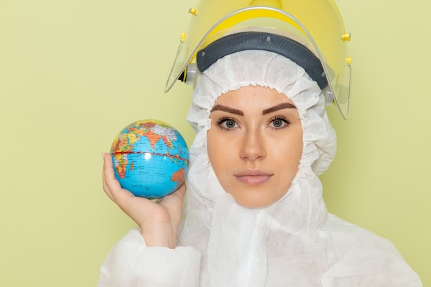 Vista frontal de perto, jovem mulher em um terno especial branco e capacete amarelo segurando um globo verde