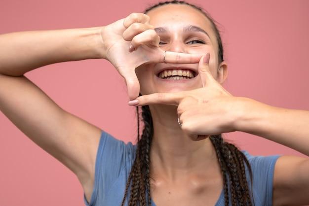 Vista frontal de perto jovem sorrindo em rosa