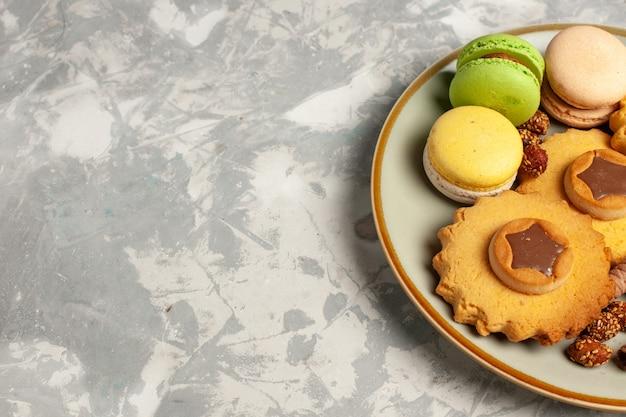 Vista frontal de perto macarons franceses com bolos e biscoitos na superfície branca