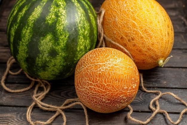 Vista frontal de perto melancia verde inteira formada por frutas frescas e suculentas com melões na mesa rústica marrom suco de frutas frescas