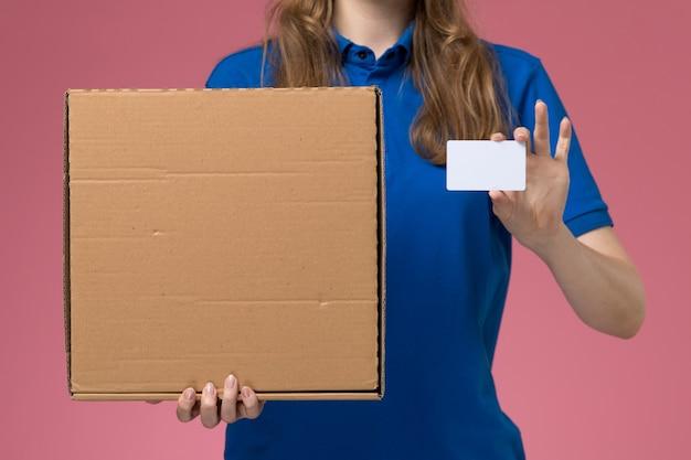 Vista frontal de perto mensageira de uniforme azul segurando uma caixa de entrega de comida e um cartão branco na mesa rosa uniforme de serviço.