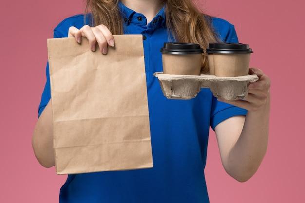 Vista frontal de perto mensageira de uniforme azul segurando xícaras de café marrom com pacote de comida em uniforme rosa claro