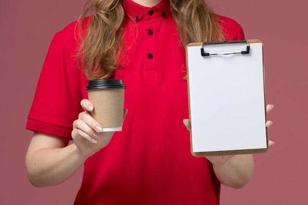 Vista frontal de perto mensageira de uniforme vermelho segurando o bloco de notas e a xícara de café rosa, uniforme de trabalho.