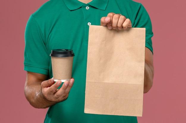 Vista frontal de perto mensageiro de uniforme verde segurando uma xícara de café de entrega e um pacote de comida em fundo rosa claro