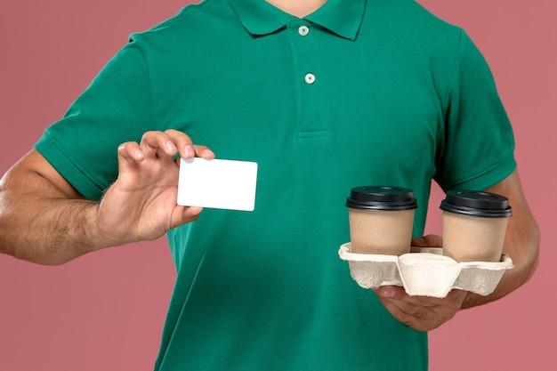 Vista frontal de perto mensageiro de uniforme verde segurando xícaras de café marrom e cartão de plástico branco sobre fundo rosa