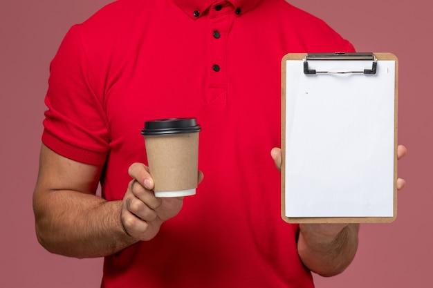 Vista frontal de perto mensageiro de uniforme vermelho segurando a xícara de café de entrega e o bloco de notas na parede rosa trabalho masculino trabalhador