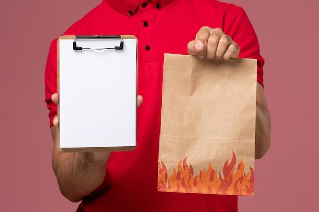 Vista frontal de perto mensageiro masculino em uniforme vermelho e capa segurando pacote de comida e bloco de notas na parede rosa serviço de entrega de uniforme de trabalho