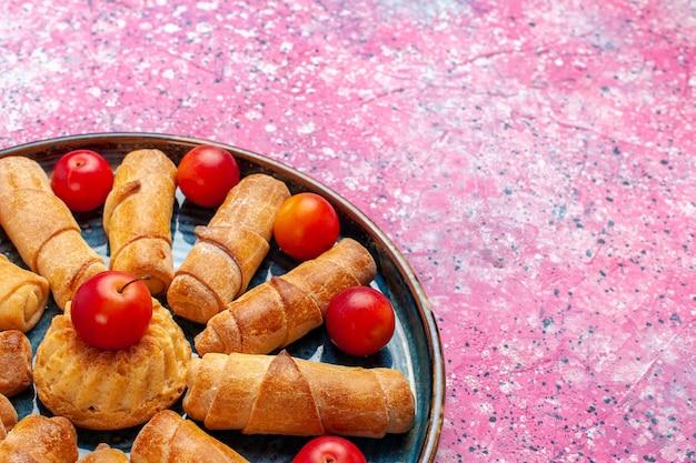 Vista frontal de perto, pães deliciosos e doces, tortas assadas dentro da bandeja com ameixas na mesa rosa