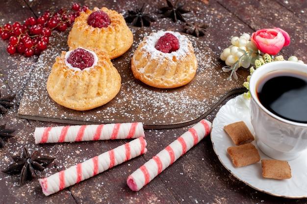 Vista frontal de perto pequenos bolos deliciosos com framboesas e cranberries junto com doces de café em mesa de madeira, bolo doce frutas assar biscoito baga