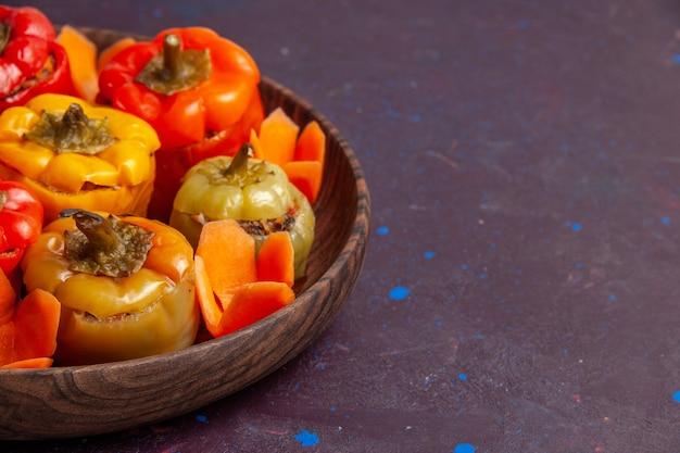 Vista frontal de perto pimentões cozidos com carne moída na superfície cinza refeição vegetais carne comida dolma