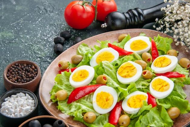 Vista frontal de perto salada de ovo com salada verde de azeitonas e tomate em fundo escuro
