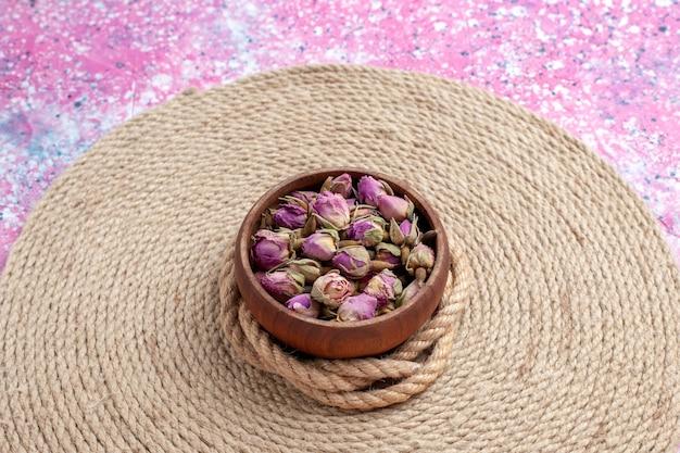 Vista frontal de perto secou pequenas flores com cordas na mesa rosa. fundo da foto a cores da flor.