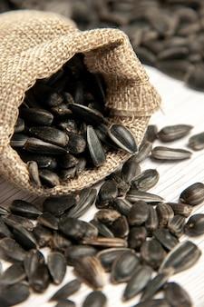 Vista frontal de perto sementes de girassol frescas sementes pretas na luz branca mesa foto óleo lanche muitas sementes