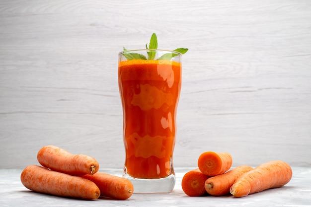 Vista frontal de perto suco de cenoura fresco dentro de um copo longo com folhas e vegetais de cenoura frescos