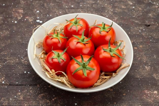 Vista frontal de perto tomates vermelhos frescos dentro de um prato branco no fundo marrom de madeira vegetal, cor de frutas