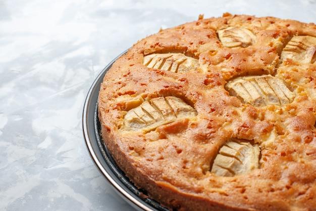Vista frontal de perto torta de maçã saborosa assada dentro da assadeira na mesa branca torta bolo biscoito doce