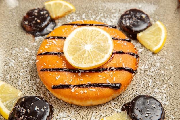 Vista frontal de perto torta deliciosa com calda de chocolate e rodelas de limão na cinza