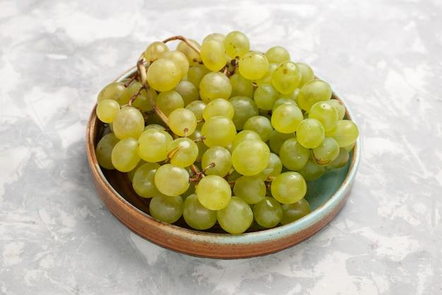 Vista frontal de perto uvas verdes frescas suculentas frutas doces suaves na mesa branca