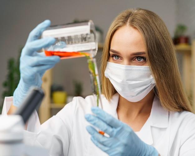 Vista frontal de pesquisadora com máscara médica no laboratório