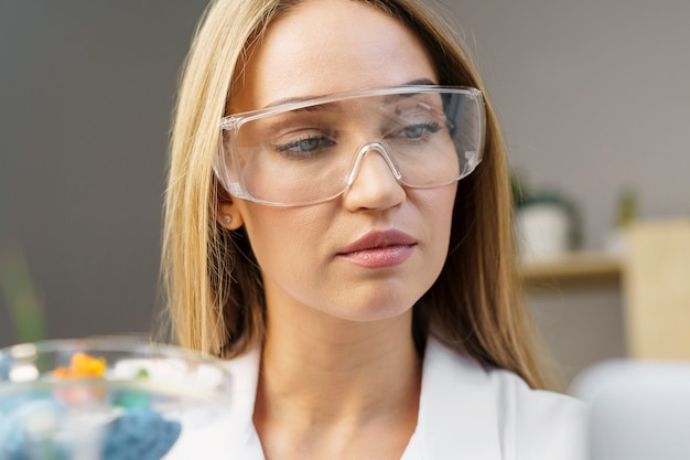 Vista frontal de pesquisadora com óculos de segurança no laboratório