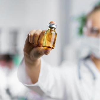 Vista frontal de pesquisadora desfocada com frasco de vacina