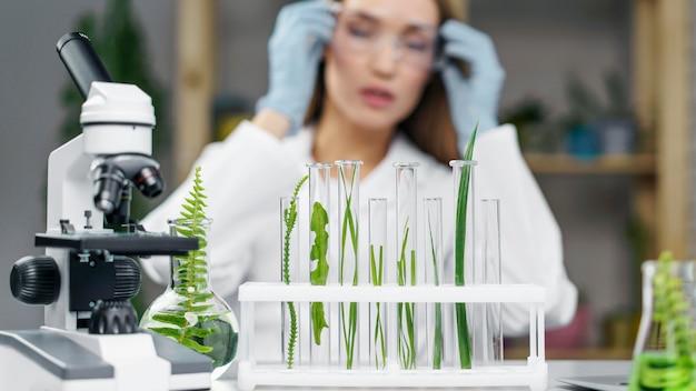 Vista frontal de pesquisadora desfocada com tubos de ensaio e microscópio