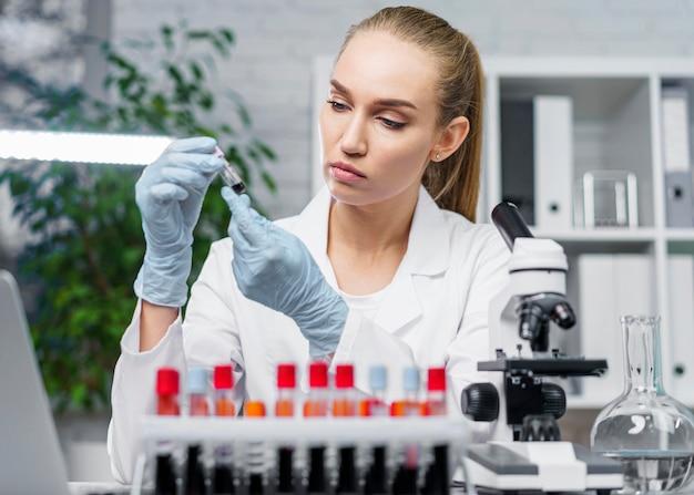 Vista frontal de pesquisadora em laboratório com tubos de ensaio e microscópio