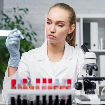 Vista frontal de pesquisadora em laboratório com tubos de ensaio