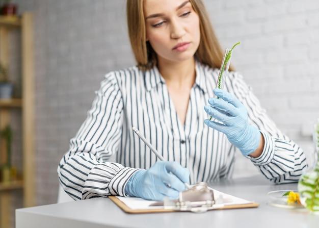 Vista frontal de pesquisadora em sua mesa com a prancheta