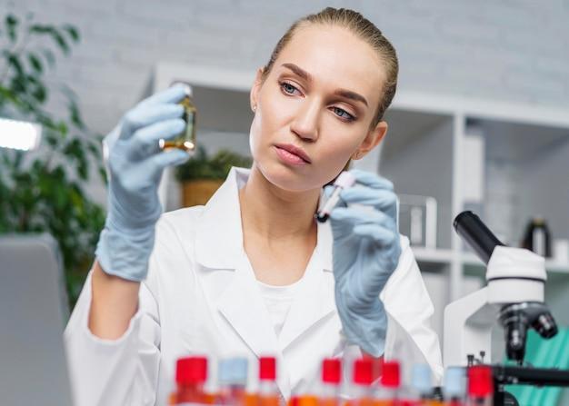 Vista frontal de pesquisadora no laboratório com microscópio e tubos de ensaio