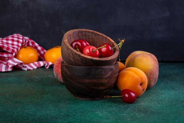 Vista frontal de pêssegos com damascos e cerejas em taças