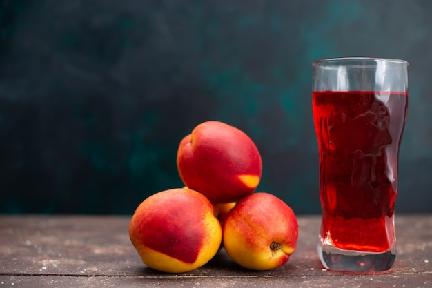 Vista frontal de pêssegos frescos com bebida frutada vermelha em superfície azul-escura suco de fruta suave fresco