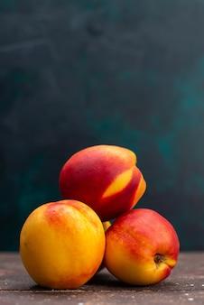 Vista frontal de pêssegos frescos, doces e suaves em frutas de parede escura, planta de árvore fresca e suave