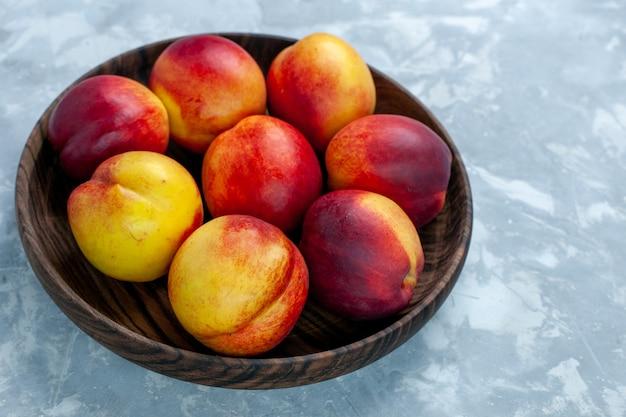 Vista frontal de pêssegos frescos maduros e frutas saborosas dentro de um prato marrom em uma mesa branca clara