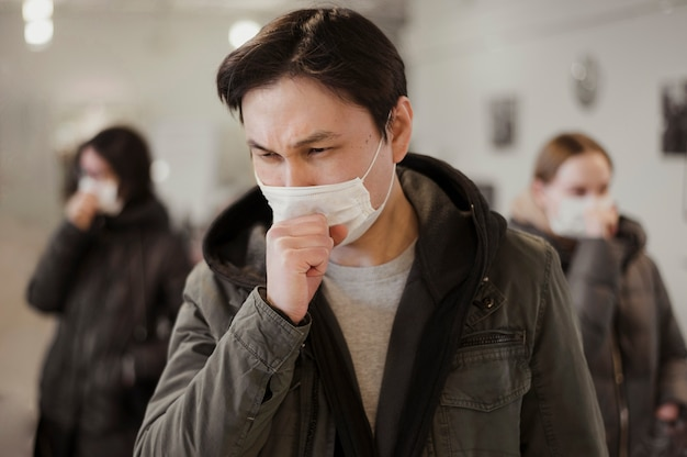 Vista frontal de pessoas com máscaras médicas tosse