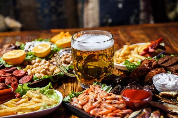 Vista frontal de petiscos de cerveja com rodelas de limão em uma barraca com um copo de cerveja