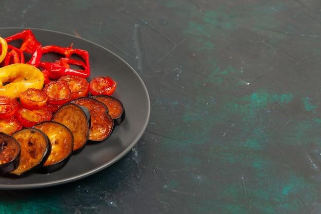 Vista frontal de pimentão cozido com berinjela na mesa verde