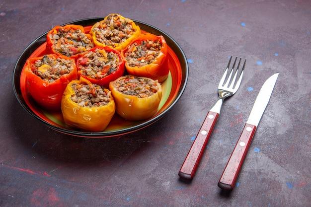 Vista frontal de pimentão cozido com carne moída misturada com temperos em uma refeição de superfície cinza dolma comida vegetais carne bovina