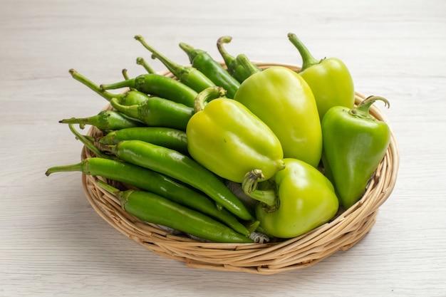 Vista frontal de pimentão verde picante com pimentão dentro da cesta no fundo branco cor foto de salada de vegetais picante quente madura