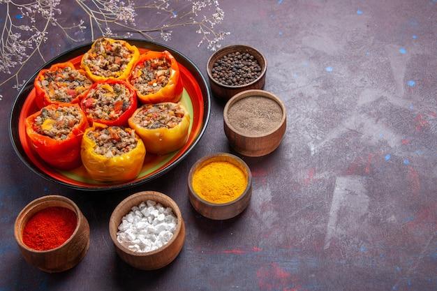 Vista frontal de pimentões cozidos com carne moída e diferentes temperos em uma refeição de superfície cinza dolma comida vegetais carne bovina