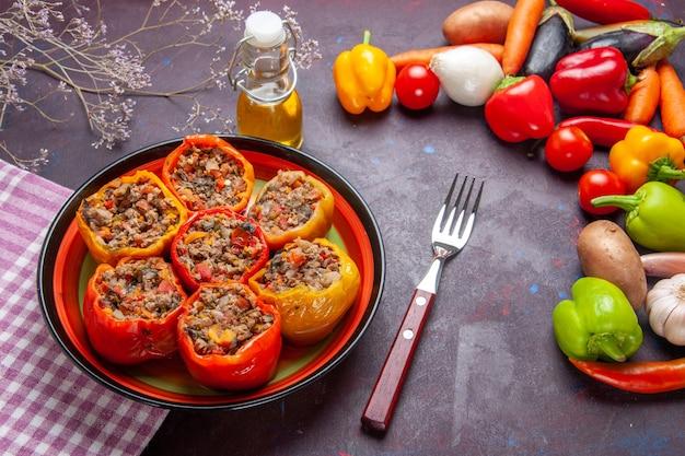Vista frontal de pimentões cozidos com carne moída e vegetais frescos na superfície escura refeição vegetais alimentos carne dolma