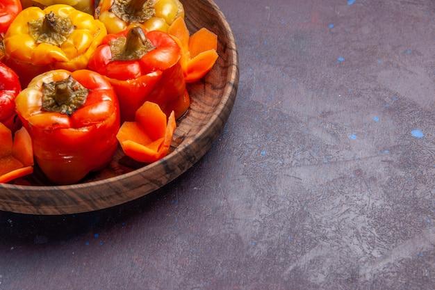 Vista frontal de pimentões cozidos com carne moída por dentro na superfície cinza refeição comida carne vegetal cozinhar