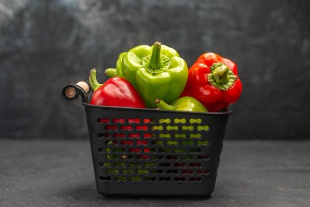 Vista frontal de pimentões frescos dentro da cesta em fundo escuro, refeição, salada, foto colorida madura