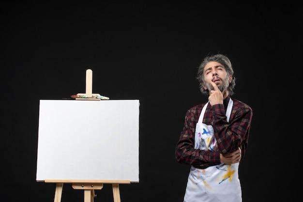 Vista frontal de pintor masculino com cavalete para desenho em pé na parede preta
