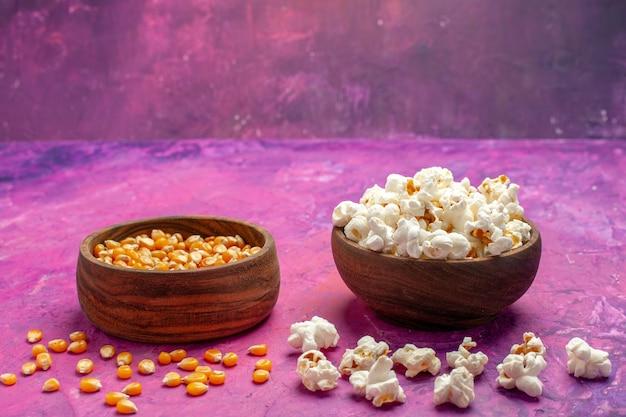 Vista frontal de pipoca fresca com grãos crus na cor rosa claro milho mesa filme cinema
